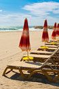 Low season beach umbrella and sun bed in the Royalty Free Stock Photos