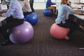 Low section of business people sitting on exercise balls while working at office
