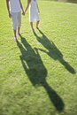 Low section of couple holding hands young while walking on grass at park Royalty Free Stock Photography