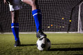 Low section of male soccer player standing with ball on field Royalty Free Stock Photo