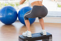 Low section rear view of a fit woman exercising on step young in gym Stock Images
