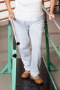 Low section of a woman walking with the help of senior support bars at hospital gym Royalty Free Stock Photos