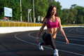 On low start pretty sporty strong slim and fit young woman athelete doing stretching exercises standing looking forward and Royalty Free Stock Photography