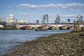 Low tide river thames and london city skyline including st paul s cathedral Stock Photography