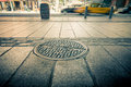 Lower manhattan manhole drain cover on streets of Stock Photo