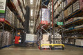 Lowering stock in a distribution warehouse using aisle truck Royalty Free Stock Photo