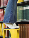 Lowsection Of Man On Stool Reaching For Book Royalty Free Stock Photo
