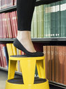 Lowsection Of Woman On Stool Reaching For Book Royalty Free Stock Photo