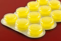 Lozenges a closeup of yellow throat in a blister pack Stock Photo