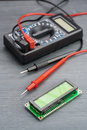 LSD screen wh1602 and multimeter on wooden background. Royalty Free Stock Photo