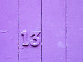 Lucky or unlucky number thirteen on purple painted wooden fence Royalty Free Stock Photo