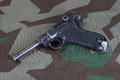 Luger p parabellum handgun on camouflaged background Royalty Free Stock Photos