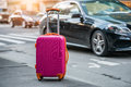 Luggage bag on the city street ready to pick by airport transfer taxi car. Royalty Free Stock Photo