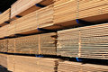Lumber at a sawmill stack of boards in yard and loader Royalty Free Stock Photos