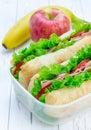 Lunch box with ciabatta bread sandwiches, apple, banana Royalty Free Stock Photo