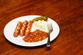 A lunch of franks and beans with cole slaw and a pickle Royalty Free Stock Photography