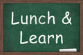 Lunch and learn education written on a chalkboard with a piece of white chalk Royalty Free Stock Photos