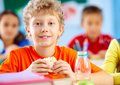 Lunch in school cheerful schoolboy looking at camera while having during break with his classmates behind Royalty Free Stock Photo
