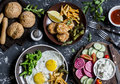 Lunch table - fried eggs, fish balls, potato chips, vegetables, sauces, homemade bread on a dark background. Royalty Free Stock Photo