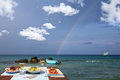 Lunch table for two by the sea with nice rainbow and clouds Royalty Free Stock Photos