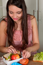 Lunchbox making smiling young woman preparing a on the kitchen table Royalty Free Stock Images