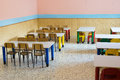 Lunchroom of the refectory of the kindergarten with small benches and small colored chairs Royalty Free Stock Image