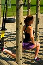 Lunge with suspension straps woman doing lunges in a playground Stock Photography