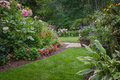 Lush backyard garden a narrow lawn path leading to a formal is flanked by a variety of colorful flowers Stock Photo