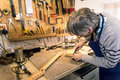 Luthier filing the neckpocket of an electric guitar Royalty Free Stock Photo