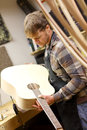 Luthier inspecting handmade guitar in workshop a young man who is a is his an acoustic that he is building Stock Photos