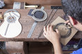 Luthier and the rosette making a guitar over a desk with cover of guitar beside him at workshop Royalty Free Stock Photos