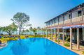 Luxuary hotel and swimming pool against palm trees blue sky Royalty Free Stock Photos
