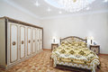 Luxurious bedroom with gilt double bed and wardrobe Royalty Free Stock Photo