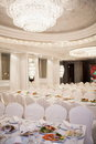 Luxurious restaurant laid tables and chairs draped with white material in Stock Photography