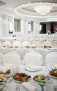 Luxurious restaurant laid tables and chairs draped with white material in Royalty Free Stock Photos