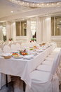 Luxurious restaurant laid tables and chairs draped with white material in Royalty Free Stock Photo