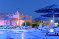 Luxurious swimming pool at night scenic view of hotel with sunbeds and parasols in foreground Stock Photography