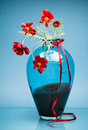 Luxurious vase with small red flowers on blue Royalty Free Stock Image