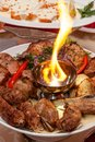 Luxuriously decorated table with roast meat and fire in the middle of the plate Royalty Free Stock Photo