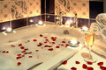 Luxury bath candlelit with rose petals and champagne Royalty Free Stock Images