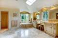 Luxury bathroom with antique vanity and cabinets spacious high vaulted ceiling velux window view of old bath tub Stock Photo