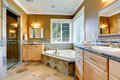 Luxury bathroom interior with corner bath tub in mustard color and two vanity cabinets Royalty Free Stock Images