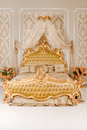 Luxury bedroom in light colors with golden furniture details. Big comfortable double royal bed in elegant classic Royalty Free Stock Photo