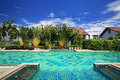 Luxury blue swimming pool in tropical garden of hotel against sky Royalty Free Stock Image