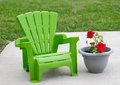 Luxury childrens chair a green child sized adirondack next to a planter on a concrete terrace kids like to relax these days too Stock Image