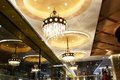 Luxury crystal chandelier lighting in hotel is lit up by led lamp bulbs a Stock Photos