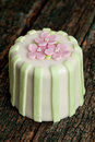 Luxury decorated mini cake with pink patels on a green background Stock Photo