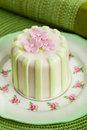 Luxury decorated mini cake with pink petals on a green background Royalty Free Stock Image