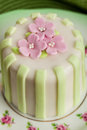 Luxury decorated mini cake with pink petals on a green background Royalty Free Stock Photo
