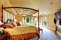 Luxury house interior beautiful bed with high posts amazing bedroom vaulted ceiling view of queen size hig and cover Stock Photography